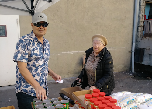 A CCDSD volunteer assists a client at our latest food distribution location in downtown San Diego.