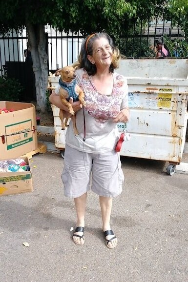 "CCDSD's ""Gate Monitors,"" Mary and her pet Chihuahua. Her infectious smile is a familiar site at our Downtown location's monthly distribution."